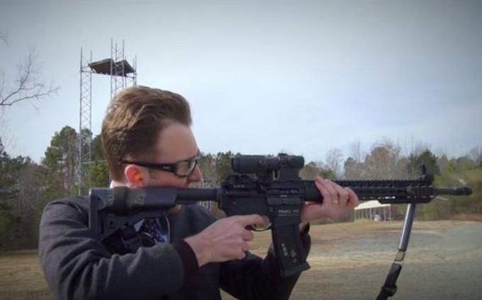 Jordan Klepper holding a rifle.